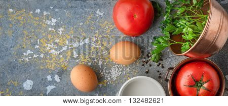 Ingredients for baked eggs with tomatoes on the stone table wide screen