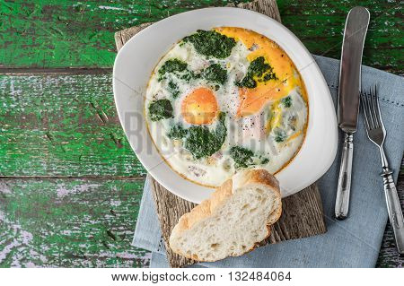 Florentine eggs with pureed spinach on the wooden table horizontal
