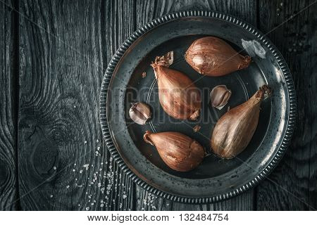 Shallot in the metal plate on the wooden table top view