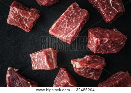 Raw angus beef slices on the black stone table top view