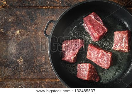 Raw angus beef in the hot pan top view