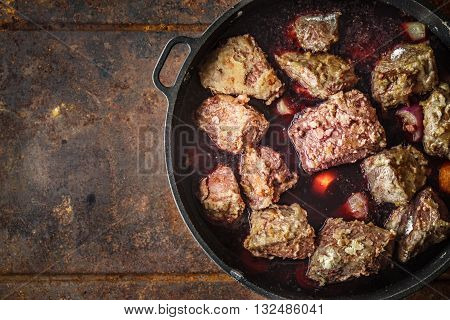 Boeuf Bourguignon in the pan on the metal background top view