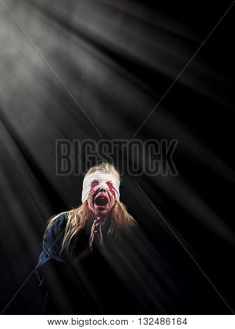 wounded scared bloody girl screaming in light rays on black background with copyspace