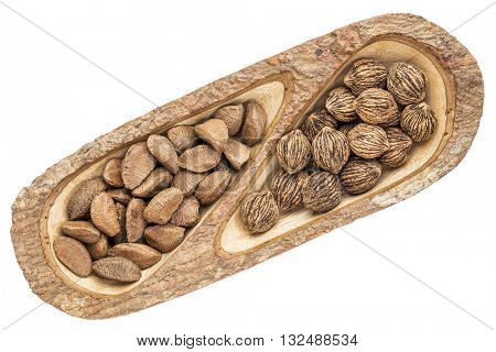 black walnuts and Brazilian nuts  in a mango wood split tray with bark edges, isolated on white, top view