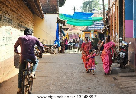 GOKARNA KARNATAKA INDIA - JANUARY 29 2016: Indian women with a girl wearing bright saris walking down in the street in Gokarna city