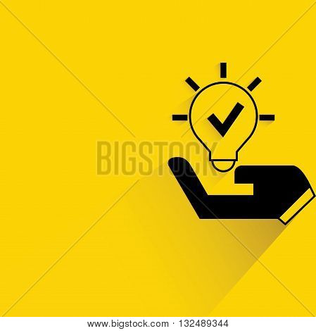 hand holding light bulb with drop shadow on yellow background
