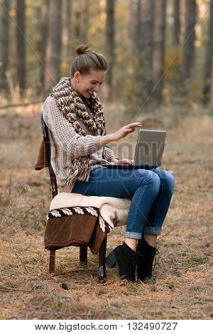 Happy, cheerful, smiling, lucky girl with computer.  Beautiful, stylish, pretty, nice, attractive, cute girl with cute smile sitting on char, plaid, works on new laptop, computer outdoor, home atmosphere, new job.