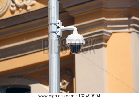 Dome Type Outdoor CCTV Camera on Street Lamp in Nice Architecture of a Church in the Background
