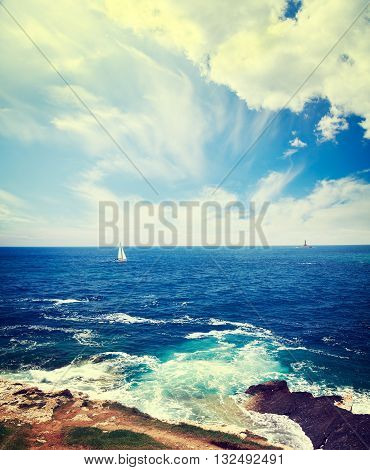 Summer Seascape with Transparent Clear Blue Water and Rocky Shore. Lighthouse and Sailing Yacht on Horizont. Sea Vacation Concept. Copy Space Background. Toned and Filtered Photo.