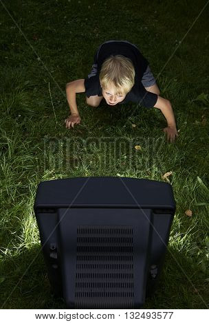 Child blond boy watching TV horror / thriller outside in the garden at night