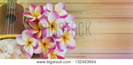 Pink Yellow And White Flowers Bunch Plumeria Or Frangipani In Vase, With Ukulele Background On Woode