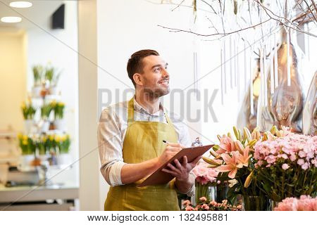 people, sale, retail, business and floristry concept - happy smiling florist man with clipboard writing and making notes order at flower shop