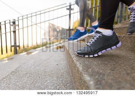 fitness, sport, people and lifestyle concept - close up of feet in shoes running downstairs in city
