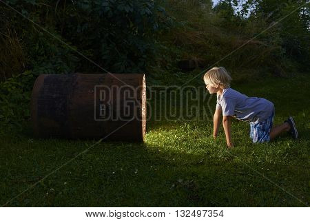 curious child boy looking into glowing hole of barrel at night