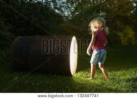 curious child girl looking into glowing hole of barrel