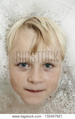 Cute little boy in bathroom with foam. Making funny faces