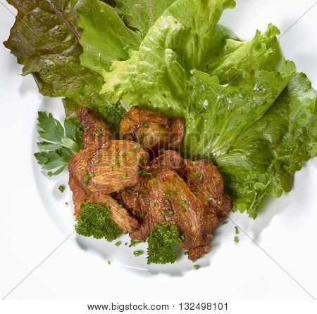 roasted chicken dish with fresh green salad on a white plate