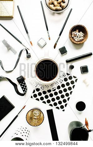 flay lay composition for bloggers artists magazines and social media. freelancer black style workspace with black coffee sketchbook napkins ribbons paintbrushes on white background.