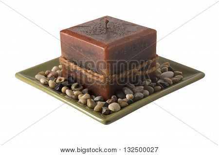 A decorative candle on a plate with stones unlit.