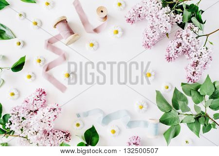 floral frame with lilac flower chamomile fresh branches and spool with blue and beige ribbon isolated on white background. flat lay top view