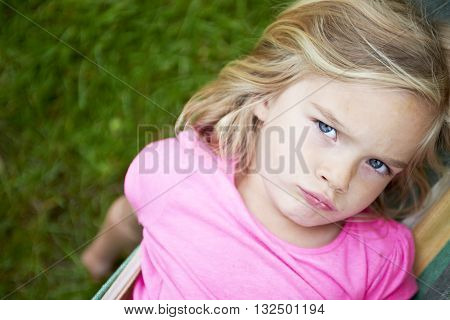Portrait of blond child girl with blue eyes looking at camera and smiling, relaxing on a colorful hammock in a home garden on summer holiday. Vacation lifestyle kid fun activities.