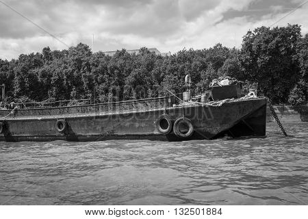 Black and white image of a rusty disused barge on the River.