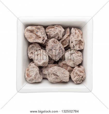 Preserved plums in a square bowl isolated on white background