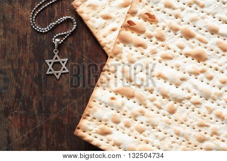 Seder concept. Star of David symbol lying near matzoh on wooden background