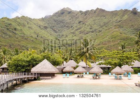 Moorea beach with beach huts and palm trees