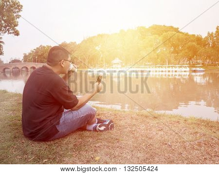 Single man happiness relax enjoy with smart phone and drink coffee at the garden under sunlight with warm / soft color tone