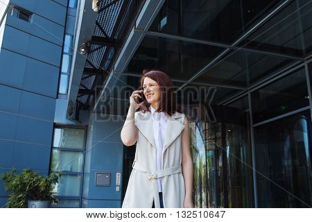 Young smiling businesswoma\n student professional outdoors talking on cell smart phone. Businesswoman smiling Life style