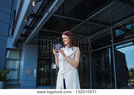 Young smiling businesswoman student professional outdoors using cell smart phone. Businesswoman smiling Life style