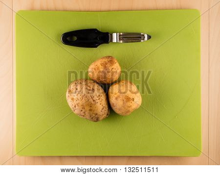 Several three unpeeled potatoes on green plastic board with peeler, simple food preparation illustration, vegetarian dieting, top view still life with center composition