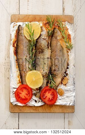 baked trout with lemon garlic rosemary pepper salt and sliced tomato
