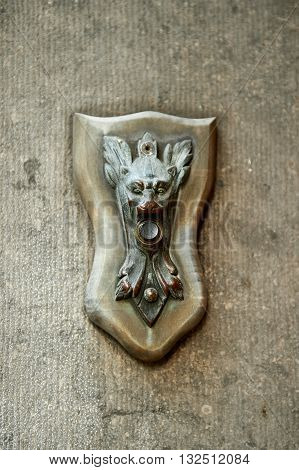 Antique vintage weathered bronze electric door bell with devil's face. Vertical orientation with copy space for text