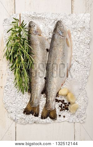 trout on aluminum foil with rosemary salt pepper corn and garlic