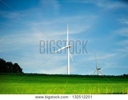 Two wind turbines - environmental protection eco tower generating electricity in green field with storm clouds in the bacground