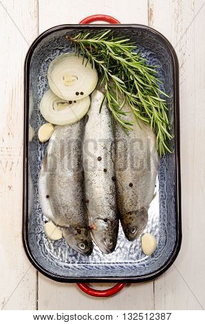 fresh trout with rosemary onion slice pepper corn and garlic in a roasting tin