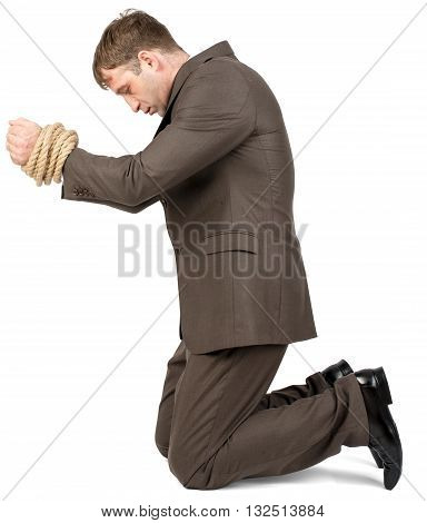 Young man kneeling with bound hands isolated on white background