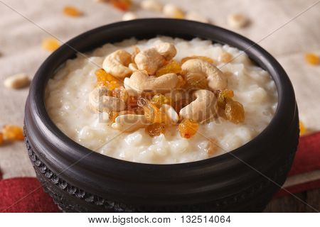 Sweet Rice Pudding With Nuts And Raisins In A Bowl Close-up. Horizontal