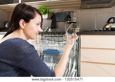 Woman using a dishwasher in a modern kitchen. Domestic appliance.