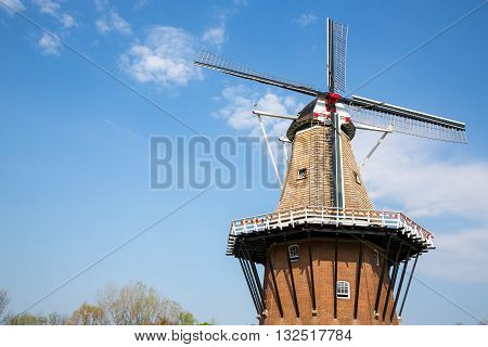 An authentic wooden windmill from the Netherlands rises behind a field of tulips in Holland Michigan at Springtime.