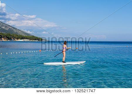 Brac Croatia - May 07 2016: female standup paddle boarder at Zlatni Rat beach Croatia