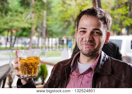Man drinking beer outdoors in a cafe with funny expressions.
