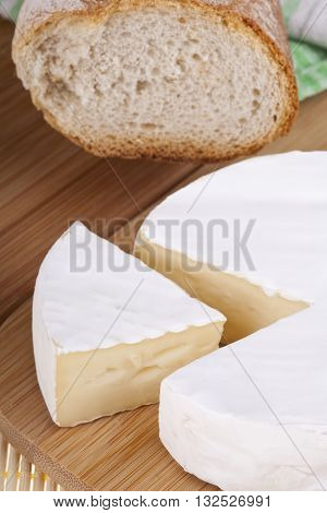 Closeup of tasty camembert cheese on a wooden desk with baguette.
