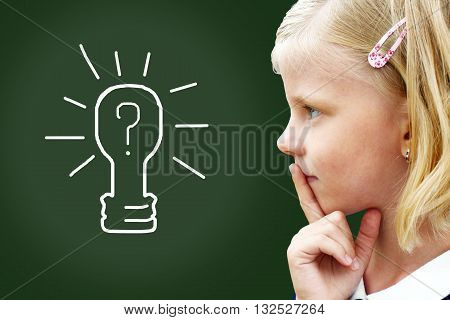 Closeup thinking child. Smart schoolchild by the blackboard thinking of light idea.