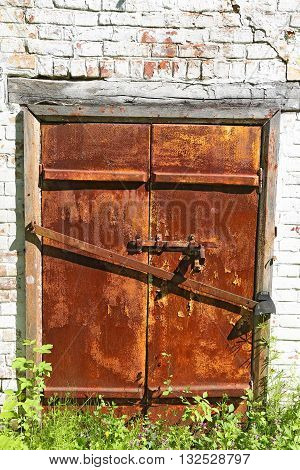 Old iron rusty door with bolt on an ancient brick wall - gated entrance to the basement