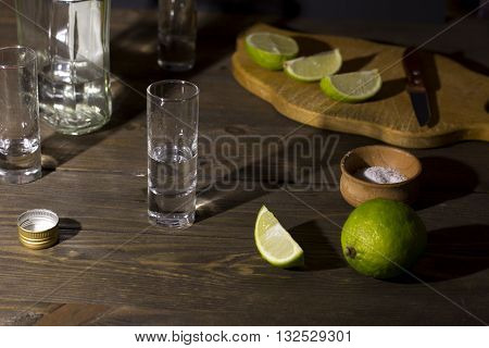 glass knife cut limes tequila on a wooden table