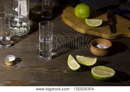 glass with tequila on a wooden table green sliced lime