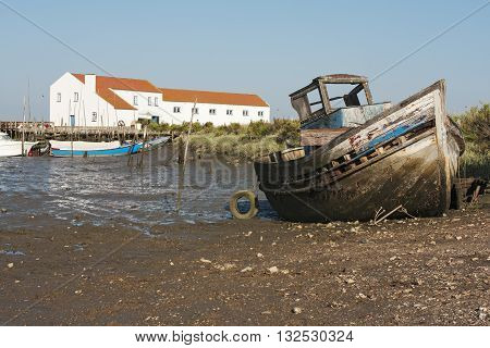 Old Fishing Trawler wooden painted and damaged stuck in the mud with a tidal mill as a background